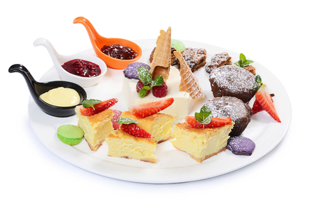 Plate of different desserts isolated on white photo
