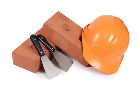 Building brick with helmet isolated on white photo