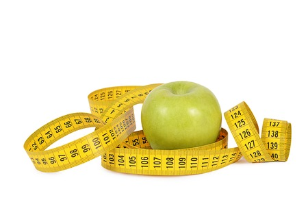 Measuring tape with apple isolated on white photo