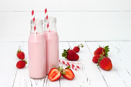 Aardbei melk in traditionele glazen flessen met rietjes op oude vintage houten achtergrond
