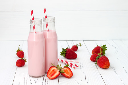 red straw: Strawberry milk in traditional glass bottles with straws on old vintage wooden background Stock Photo