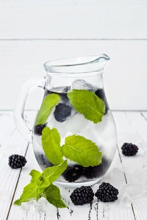 Healthy detox water with blackberry and mint. Cold refreshing berry drink with ice on white wooden table. Copy space background Stock fotó