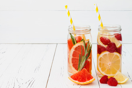 Detox fruit infused flavored water. Refreshing summer homemade cocktail. Copy space background Reklamní fotografie