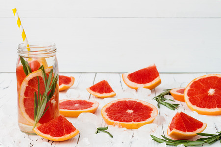 fruit in water: Detox fruit infused flavored water. Refreshing summer homemade cocktail Stock Photo