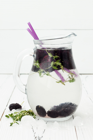 water thyme: Healthy detox water with mulberry. Cold refreshing berry drink with ice and thyme on white wooden table.