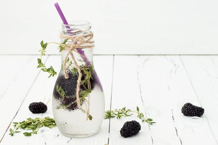 water thyme: Healthy detox water with mulberry. Cold refreshing berry drink with ice and thyme on white wooden table. Copy space background Stock Photo