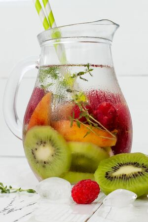 water thyme: Healthy detox fruit infused flavored water. Summer refreshing homemade cocktail with fruits and thyme on white wooden table Stock Photo
