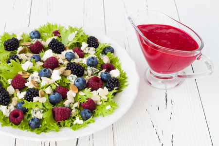 raspberries: Summer refreshing mixed berry salad with pumpkin seeds, blue cheese, feta and sweet red raspberry vinaigrette Stock Photo