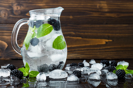 Healthy detox flavored water with blackberry and mint. Cold refreshing berry drink with ice on dark wooden table. Copy space background