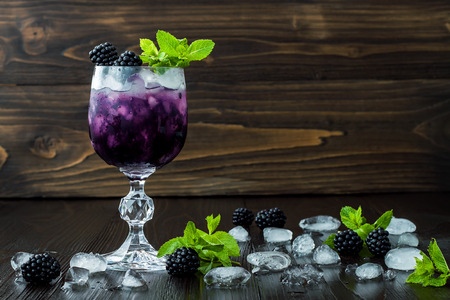 Tasty blackberry cocktail in wine glass with mint and ice on dark wooden table. Summer berry lemonade. Copy space background 스톡 콘텐츠