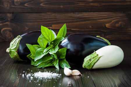 Purple and white eggplant aubergine with basil and garlic on dark wooden table. Fresh raw farm vegetables - harvest from the garden in rustic kitchen. Rural still life Stock Photo
