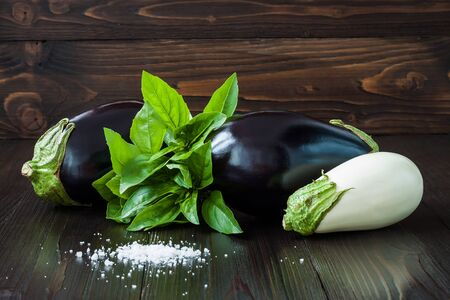 rustic kitchen: Purple and white eggplant aubergine with basil on dark wooden table. Fresh raw farm vegetables - harvest from the garden in rustic kitchen. Rural still life Stock Photo