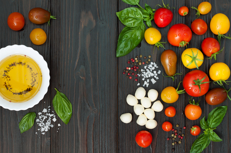 oil color: Cherry tomatoes of various color, mozzarella, basil leaves, spices and olive oil from above over dark wooden table. Italian caprese salad recipe ingredients. Top view, free text copy space
