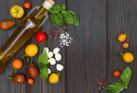 Cherry tomatoes of various color, mozzarella, basil leaves, spices and olive oil from above over dark wooden table. Italian caprese salad recipe ingredients. Top view, free text copy space