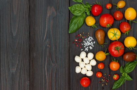 ensalada tomate: Cherry tomatoes of various color, mozzarella, basil leaves, spices from above over dark wooden table. Italian caprese salad recipe ingredients. Top view, free text copy space