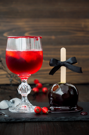 Spooky bloody cocktail and black poison caramel apple. Traditional dessert and drink recipe for Halloween party. Selective focus Stock fotó