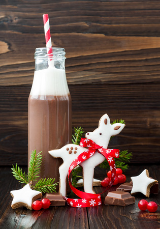 gingerbread cookie: Hot chocolate with whipped cream in old-fashioned retro bottles with red striped straws. Christmas holiday drink and gingerbread baby deer or fawn cookies. Free text copy space