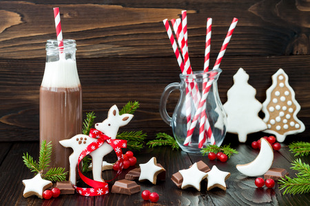 Hot chocolate with whipped cream in old-fashioned retro bottles with red striped straws. Christmas holiday drink and gingerbread baby deer or fawn cookies