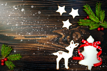 gingerbread cookies: Christmas holiday background with gingerbread cookies and fir branches on the old wooden board. Copy space. Toned Stock Photo