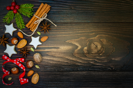 christmas spices: Christmas holiday background with gingerbread cookies, spices and fir branches on the old wooden board. Copy space. Toned Stock Photo
