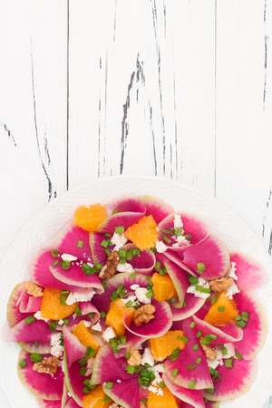 Colorful and healthy watermelon radish, orange and goat cheese carpaccio salad. Top view, free text copy space