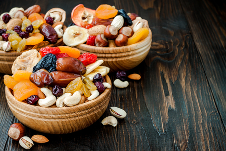 Mix of dried fruits and nuts on dark wood background with copy space. Symbols of judaic holiday Tu Bishvat