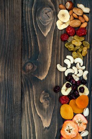 복사 공간 어두운 나무 배경에 말린 과일과 견과류의 혼합. 평면도. 유태교 휴일 화 Bishvat의 상징