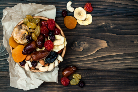 shvat: Mix of dried fruits and nuts on a dark wood background with copy space. Top view. Symbols of judaic holiday Tu Bishvat Stock Photo
