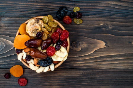 Mix of dried fruits and nuts on a dark wood background with copy space. Top view. Symbols of judaic holiday Tu Bishvat Standard-Bild