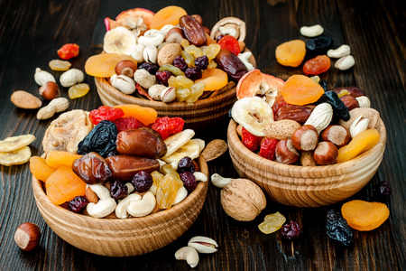 Mix of dried fruits and nuts on dark wood background. Symbols of judaic holiday Tu Bishvat