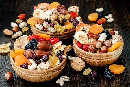 어두운 나무 배경에 말린 과일과 견과류의 혼합. 유태교 휴일 화 Bishvat의 상징 스톡 콘텐츠
