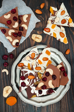 shvat: Holiday chocolate bark with dried fruits and nuts on a dark wood background. Top view. Dessert recipe for judaic holiday Tu Bishvat