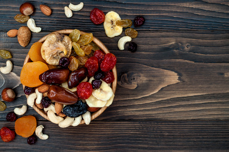 Mix of dried fruits and nuts on a dark wood background with copy space. Top view. Symbols of judaic holiday Tu Bishvat 免版税图像