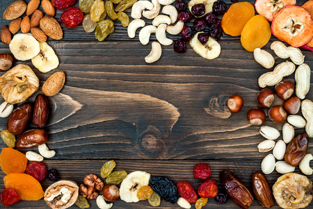 Mix of dried fruits and nuts on a dark wood background with copy space. Top view. Symbols of judaic holiday Tu Bishvat 스톡 콘텐츠
