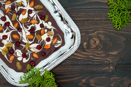 shvat: Holiday chocolate bark with dried fruits and nuts on a dark wood background with copy space. Top view. Dessert recipe for judaic holiday Tu Bishvat Stock Photo