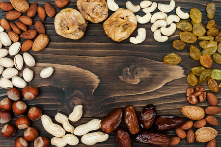 shvat: Mix of dried fruits and nuts on a dark wood background with copy space. Top view Stock Photo