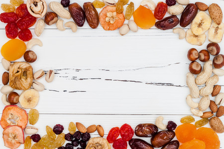 rustic food: Mix of dried fruits and nuts on a white vintage wood background with copy space. Top view. Symbols of judaic holiday Tu Bishvat