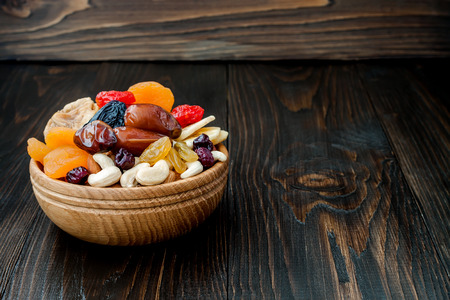 shvat: Mix of dried fruits and nuts on dark wood background with copy space. Symbols of judaic holiday Tu Bishvat