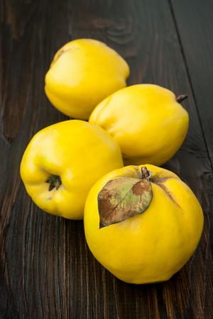 quinces: Ripe quinces on vintage wooden table.