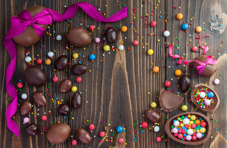Chocolate Easter eggs over rustic wooden background. Copy space