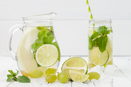 lime: Refreshing homemade lime and mint cocktail over old vintage wooden table. Detox fruit infused flavored water. Clean eating. Copy space background Stock Photo