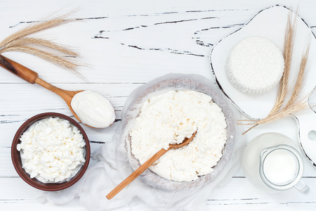 shavuot: Soft homemade fresh ricotta cottage cheese made from milk, draining on muslin cloth. Tzfat cheese with wheat grains. Symbols of judaic holiday Shavuot.