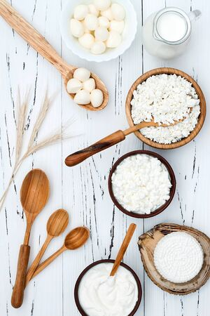 judaic: Soft homemade fresh ricotta cottage cheese made from milk, draining on muslin cloth. Tzfat cheese with wheat grains. Symbols of judaic holiday Shavuot.