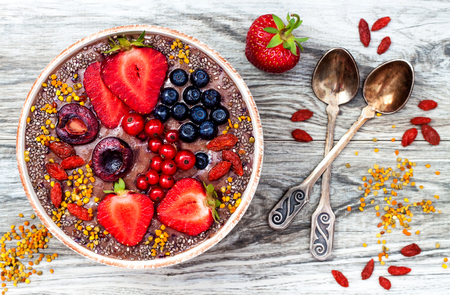 Acai ontbijt superfoods smoothies kom met chia zaden, stuifmeel, toppings goji bessen en pindakaas. Overhead, bovenaanzicht.