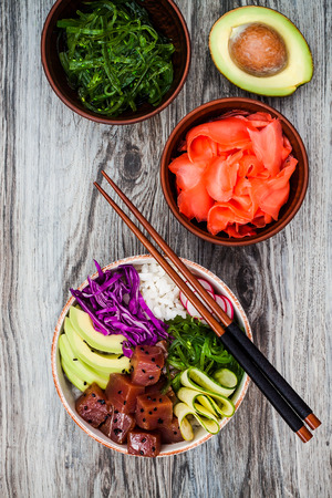 Hawaiian tuna poke bowl with seaweed, avocado, red cabbage, radishes and black sesame seeds