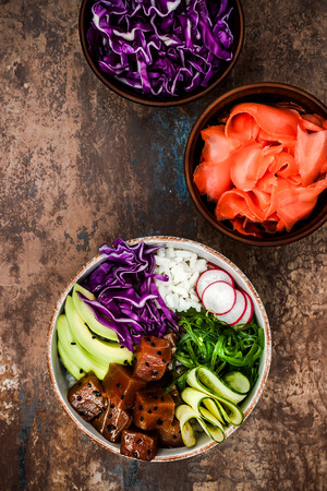 poke: Hawaiian tuna poke bowl with seaweed, avocado, red cabbage, radishes and black sesame seeds