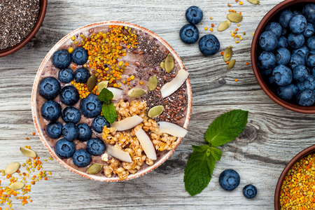 Acai breakfast superfoods smoothies bowl topped with chia, flax and pumpkin seeds, bee pollen, granola, coconut flakes and blueberries. Overhead, top view, flat lay Stock fotó