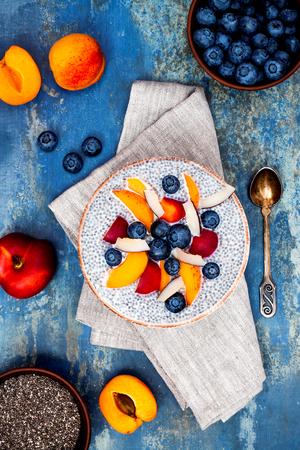 Detox en gezonde superfoods ontbijt kom concept. Vegan kokosmelk chia zaden pudding over de blauwe stenen tafel met verschillende vruchten en bosbessen. Overhead, bovenaanzicht, plat. Stockfoto