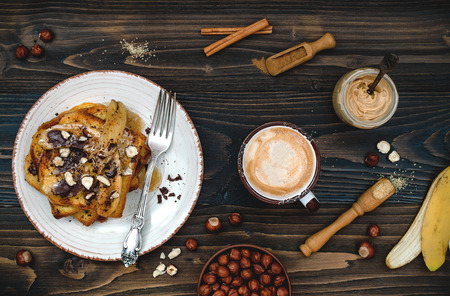 comida de navidad: Preparing healthy fall and winter breakfast. Vegan vanilla french toast with caramelized bananas, raw dark chocolate and hazelnut butter. Overhead, top view, flat lay. Rustic country style. Ideal Christmas morning meal concept. Toned image Foto de archivo