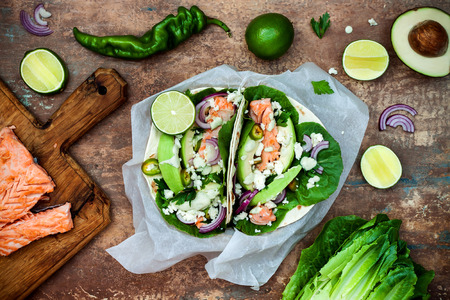 Preparing healthy lunch snacks. Fish tacos with grilled salmon, red onion, fresh salad leaves and avocado cilantro sauce on vintage stone background. Recipe for Cinco de Mayo party. Top view. Stock Photo